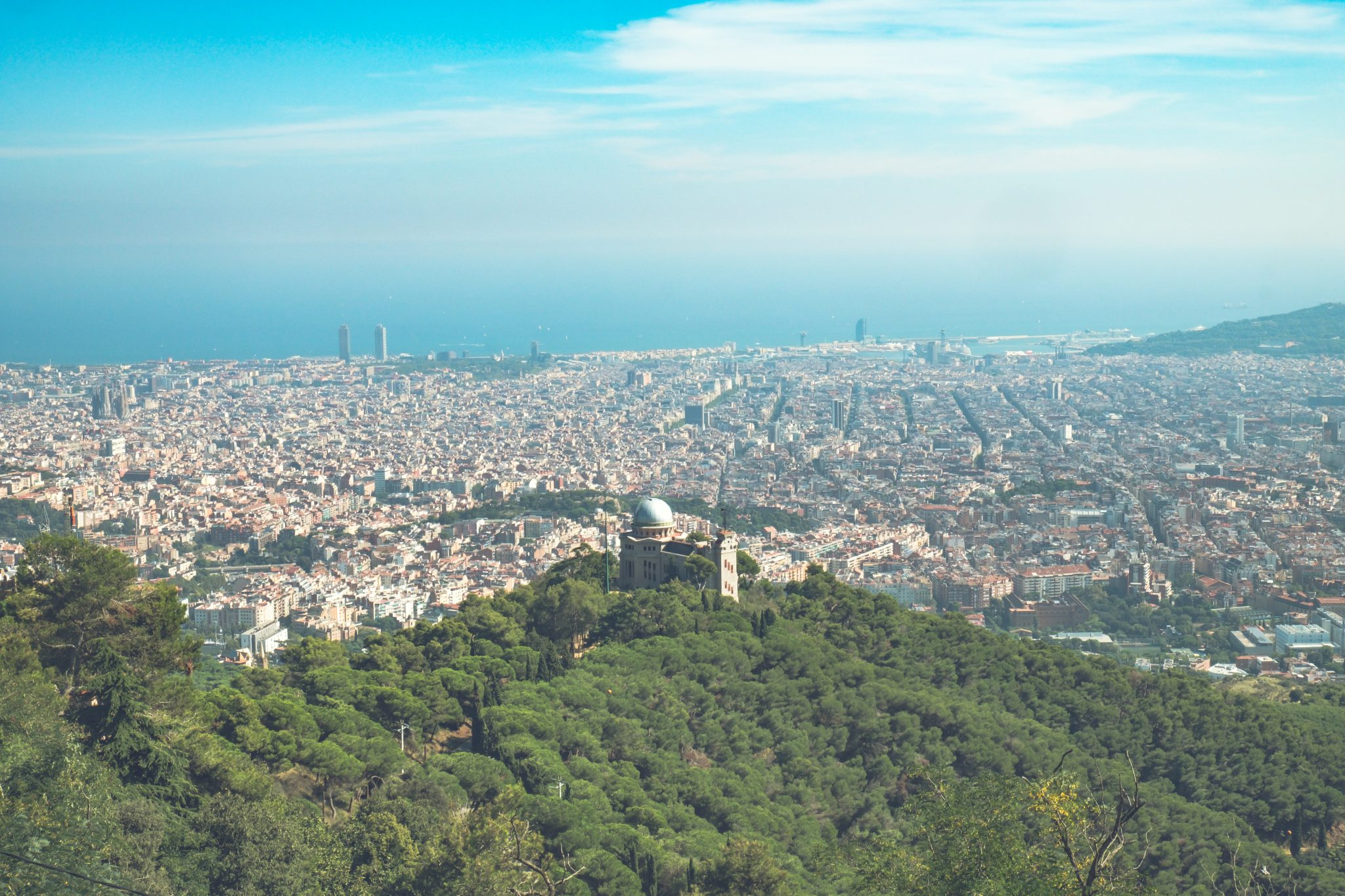 Panoramic view of barcelona with trees in the foreground and the sea in the background photo by Jo Kassis