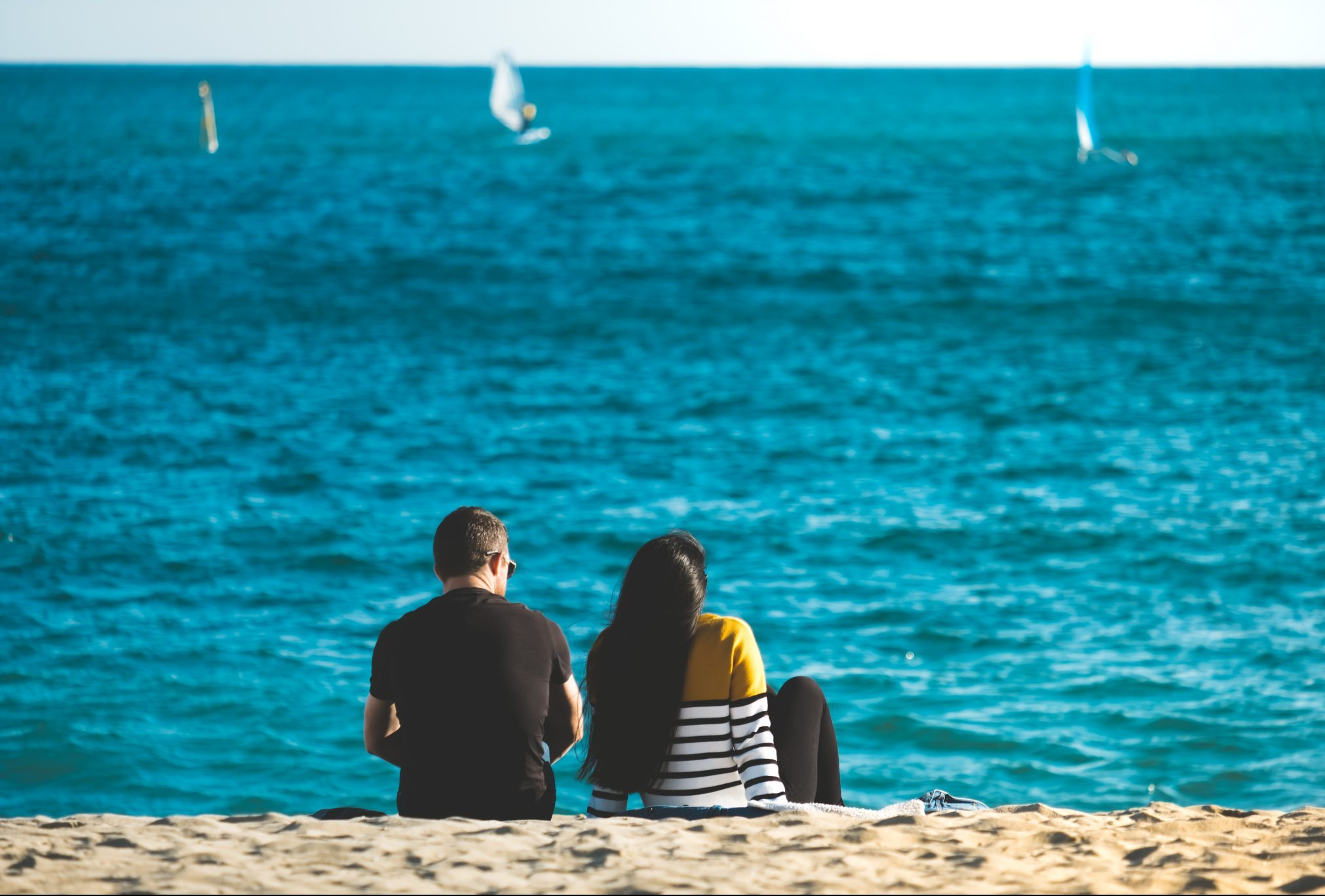 Couple sitting at the beach looking at the sea photo by Jo Kassis