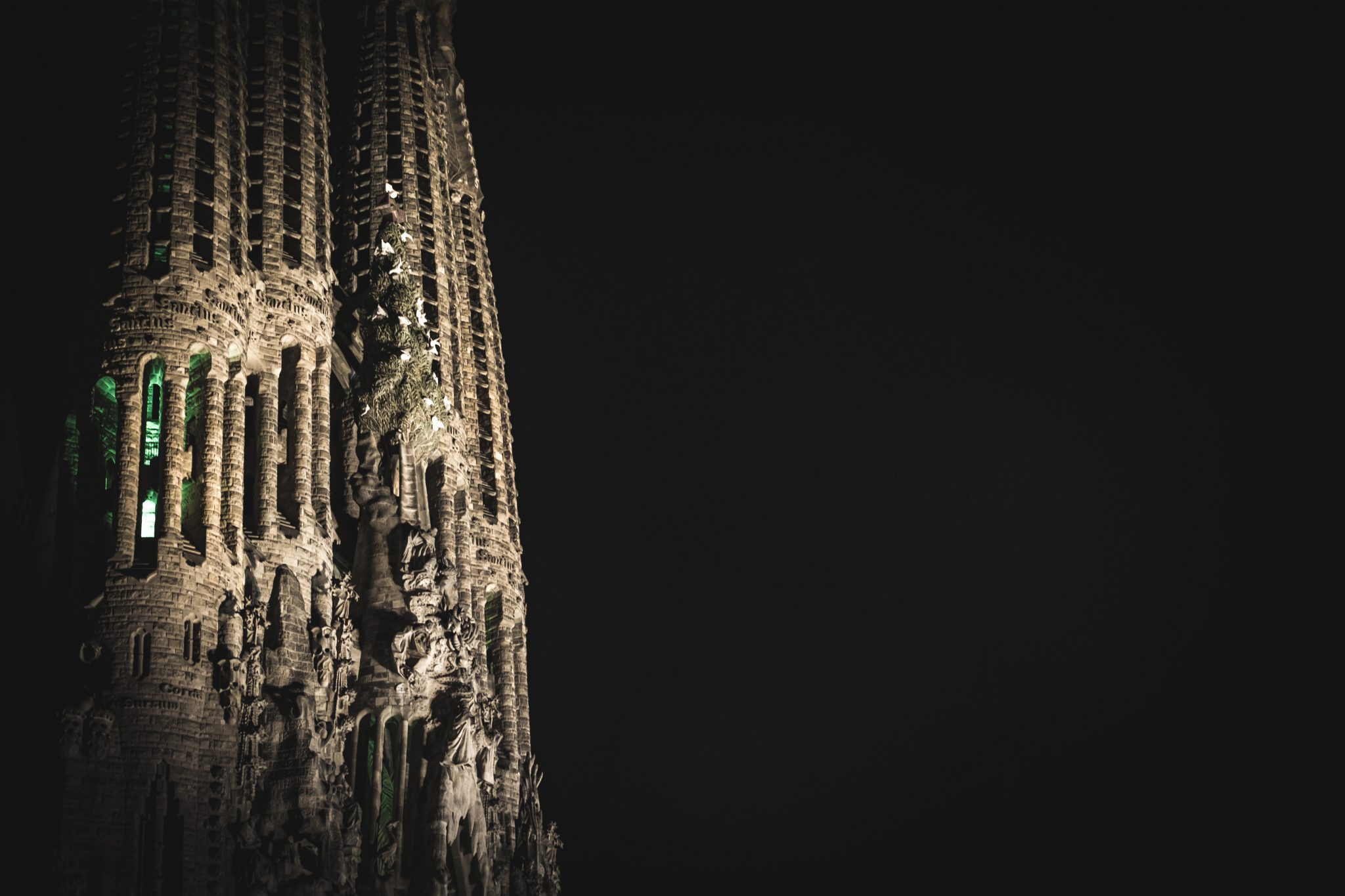 Dramatic view of the facade of La Sagrada Familia at illuminated night photo by Jo Kassis