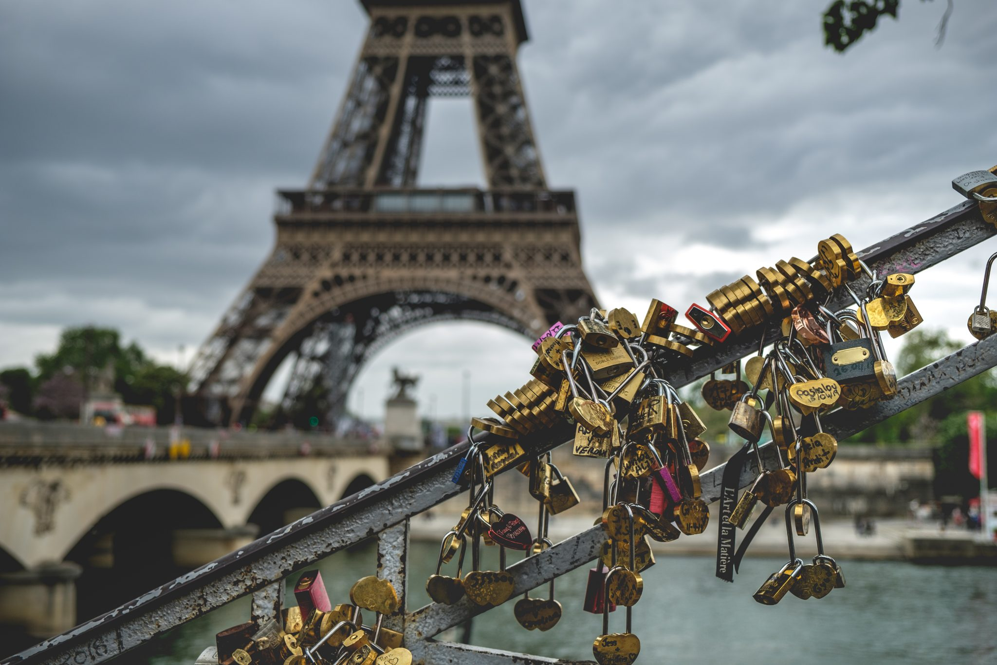 Lockpads on a hand rail next to the Seine with the eiffel tower in the background photo by Jo Kassis