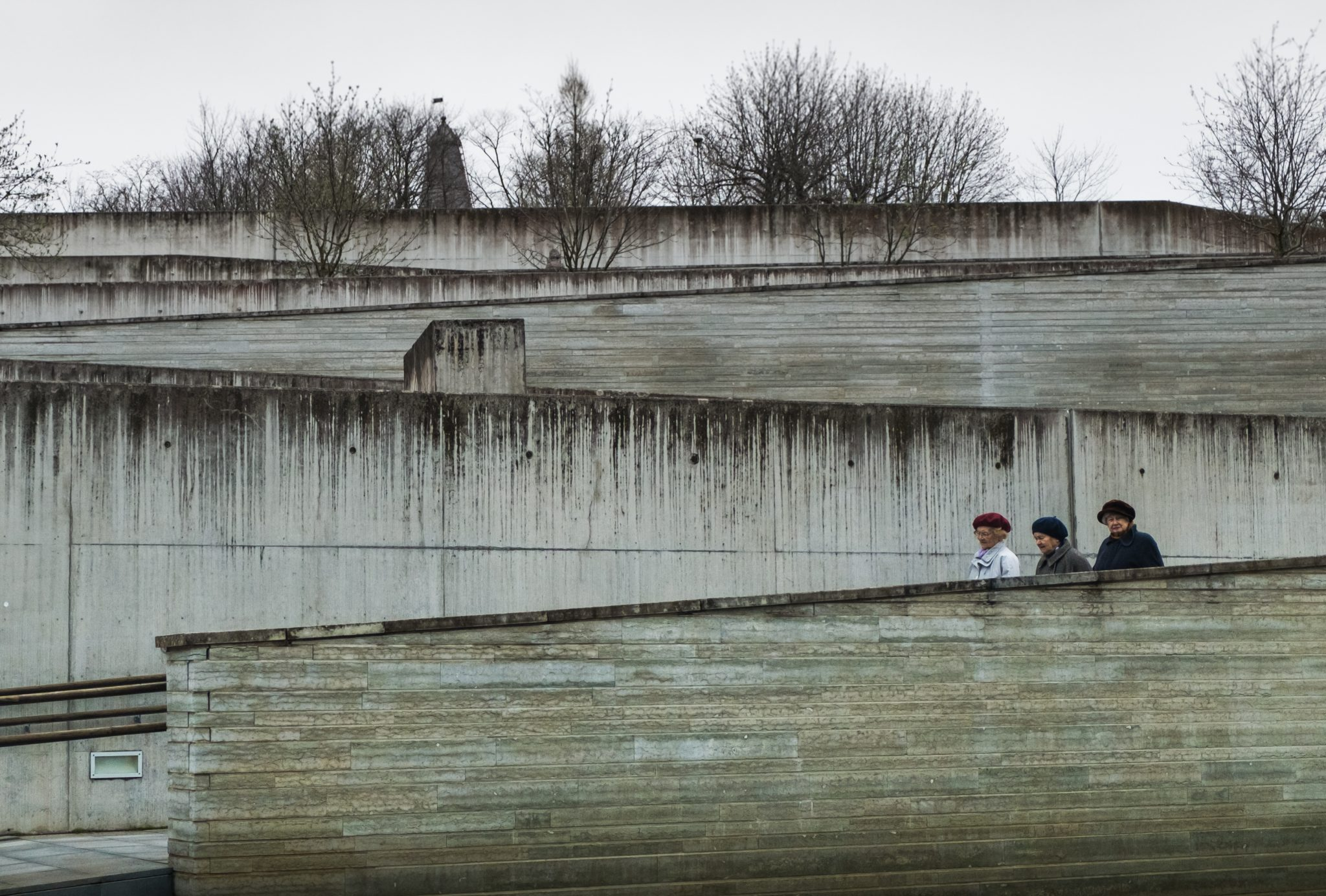 Three elderly ladies walking down a concrete structure ramp in front of the KUMU museum in Tallinn photo by Jo Kassis