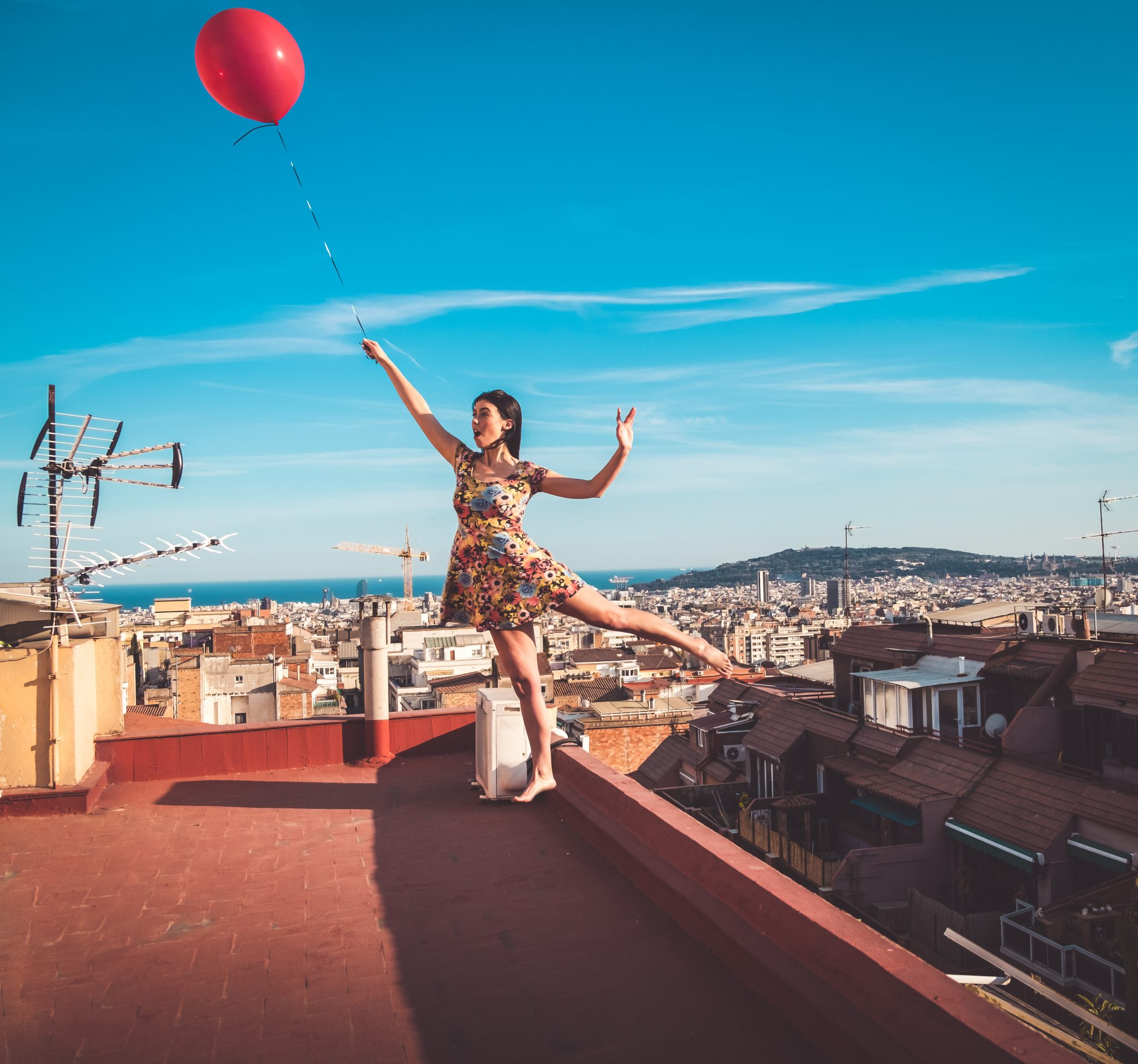 Lemonbahaya model posing for creative levitation with red balloon over barcelona photo by Jo Kassis