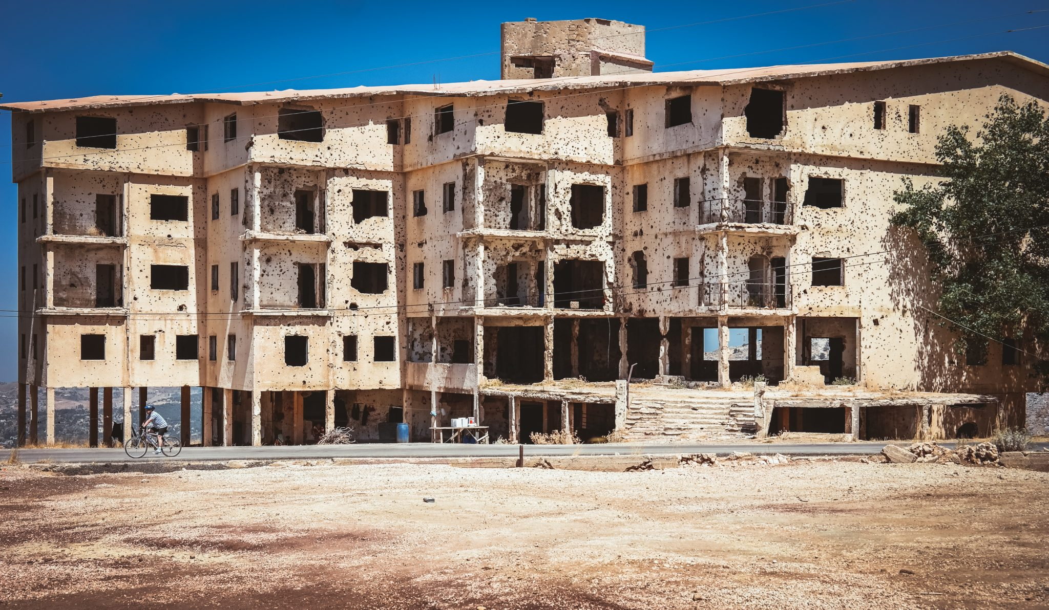 War destroyed hotel with bullet holes with a bike passing by in Qanat Bakish Lebanon Photo by Jo Kassis