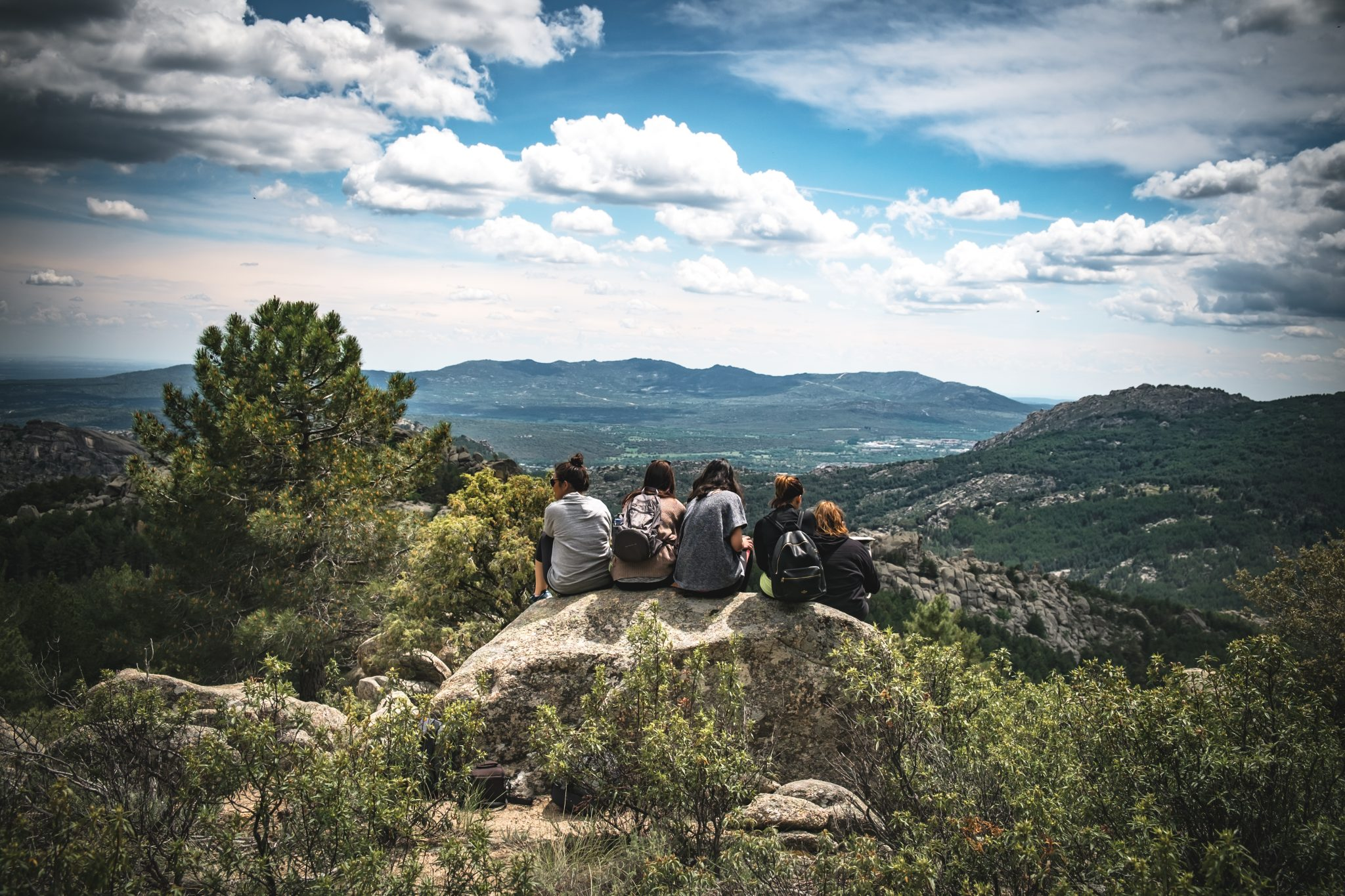 Four girls sitting on a rock look at the view in cercedilla photo by Jo Kassis