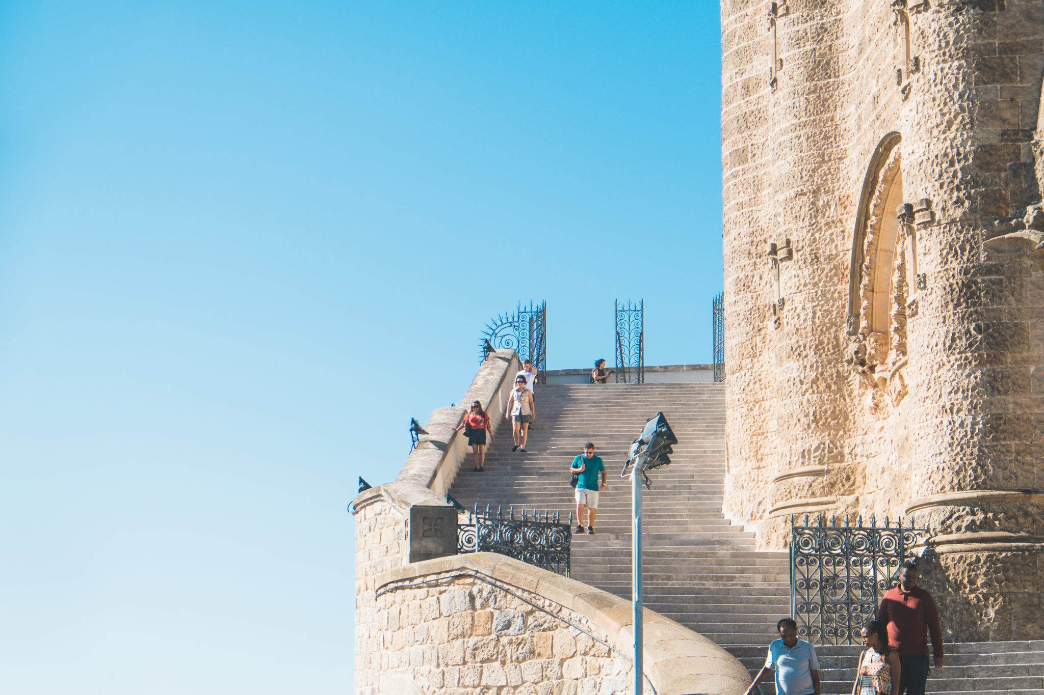 People on the stairs with blue sky photo by Jo Kassis
