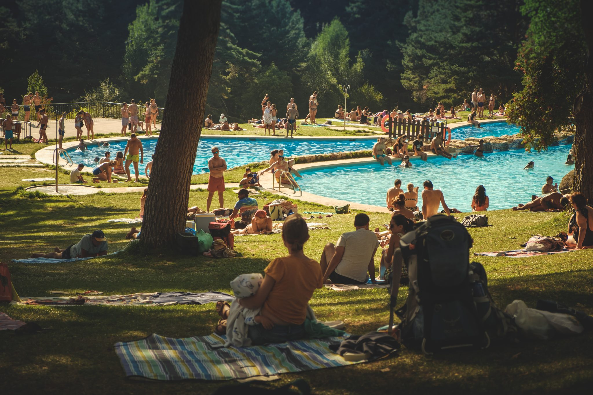 People relaxing on the grass by a natural pool in cercedilla photo by Jo Kassis