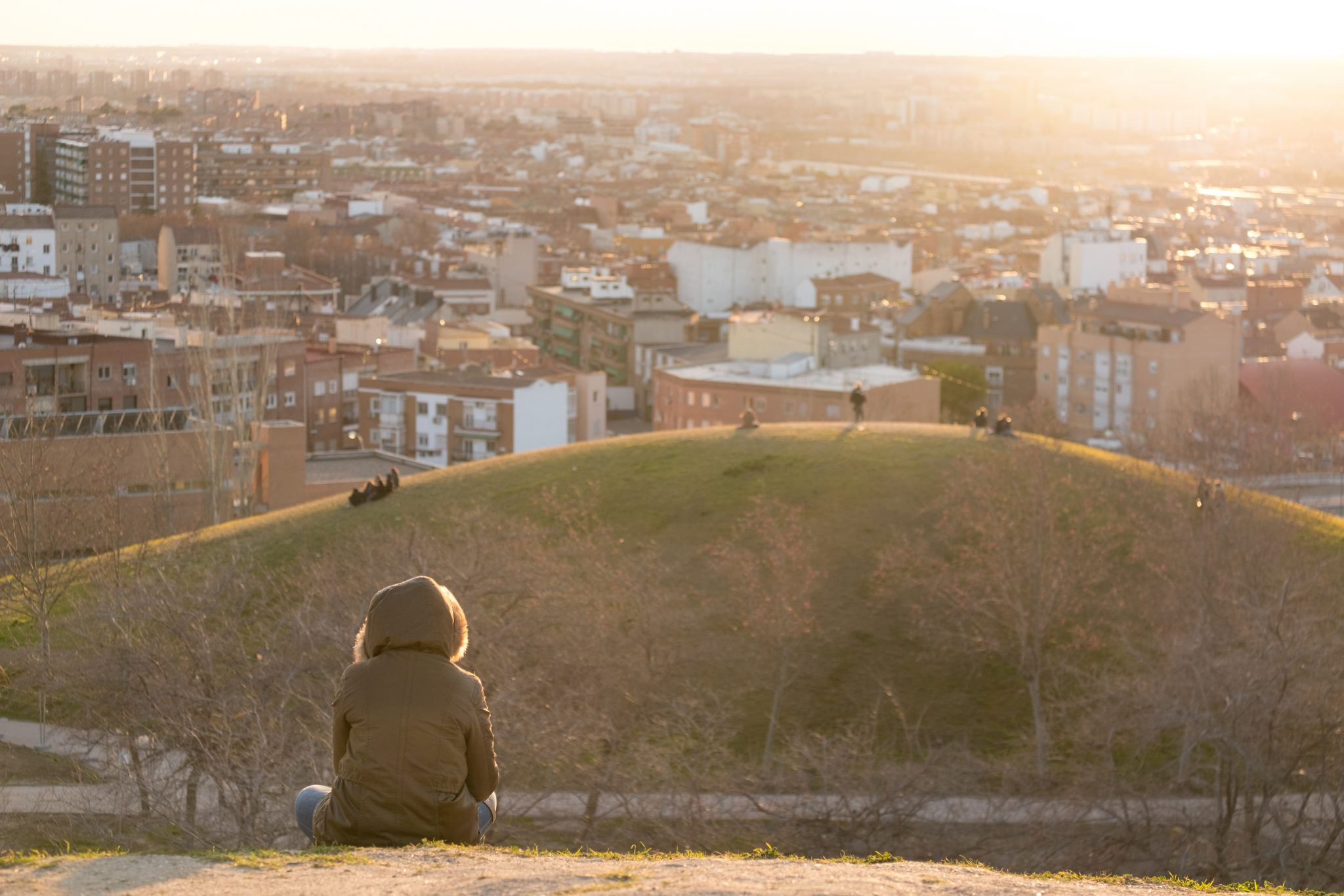 A women sitting in the parque de las siete tetas at sunset with the city of Madrid in the background photo by Jo Kassis