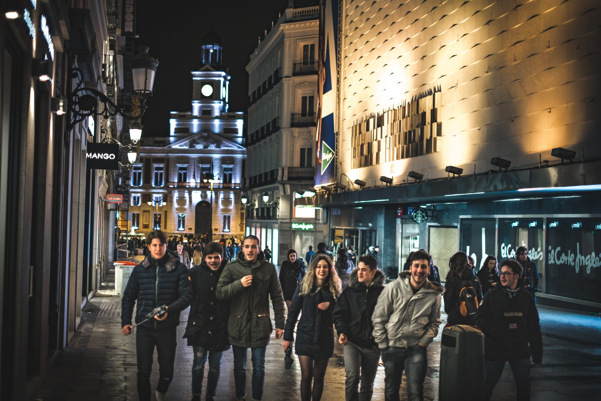 Group of young people walking in the streets of Madrid at night photo by Jo Kassis