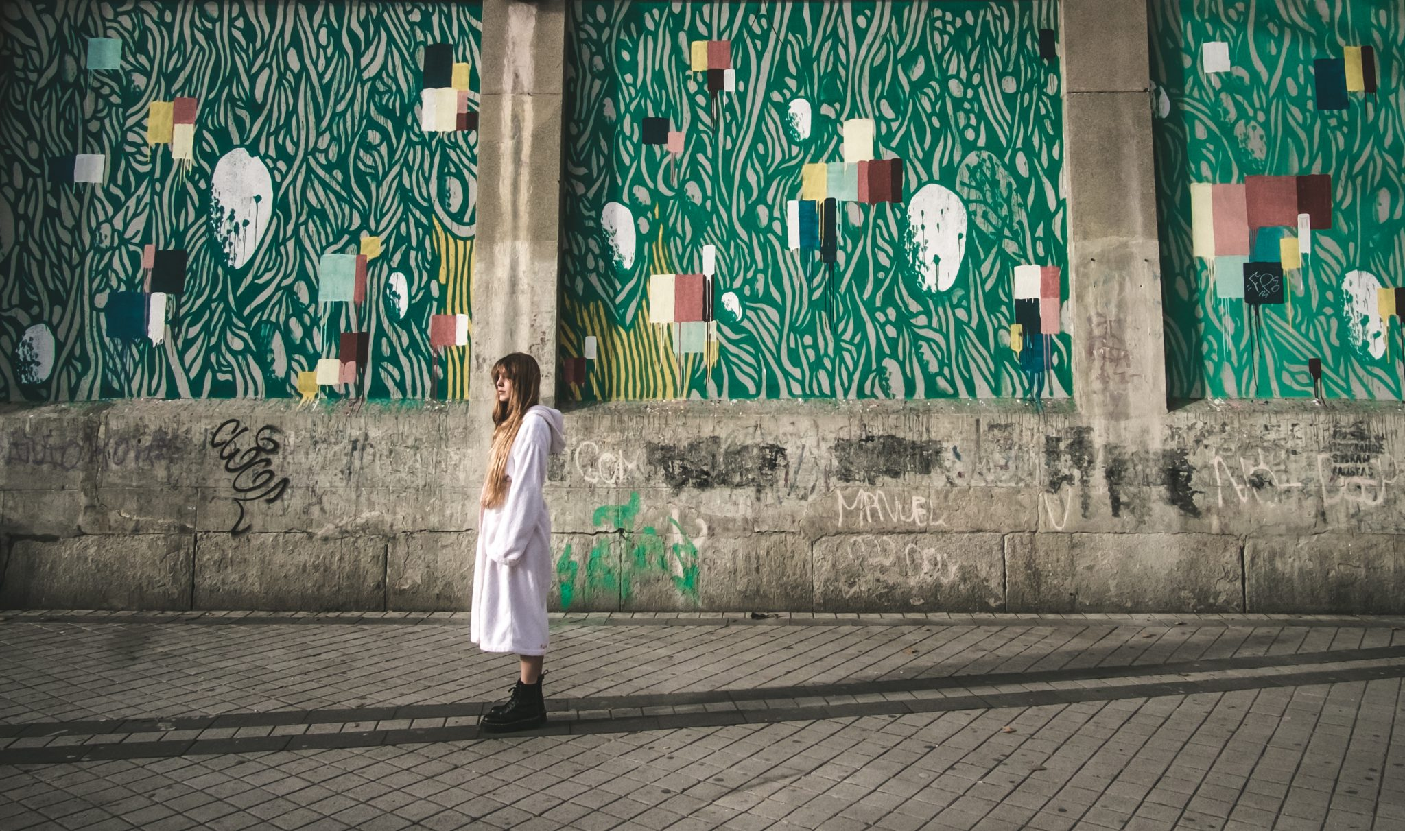 Young women posing in front of a painted wall at the tabacalera of madrid photo by jo Kassis