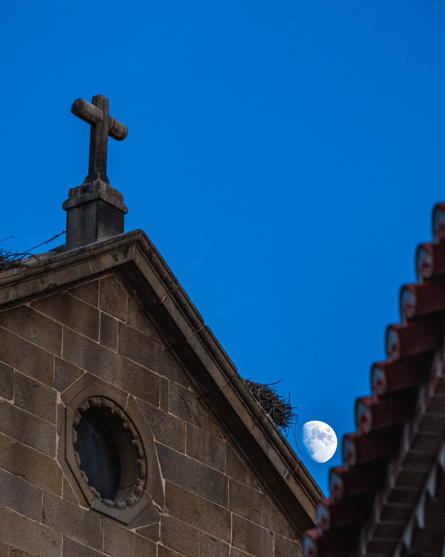 Cross made of stone on top of a church at night with moon in the background photo by Jo Kassis