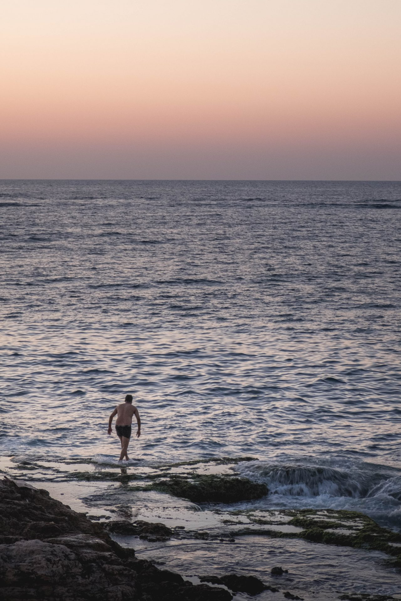 Men swimming at sunset in the bay of Raouche in Beirut photo by Jo Kassis
