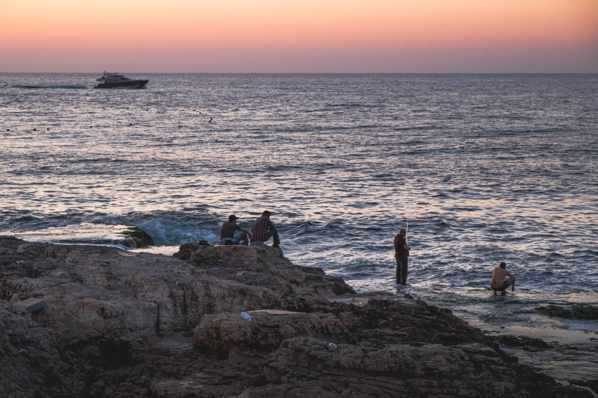 People swimming and fishing at sunset in the bay of Raouche in Beirut photo by Jo Kassis