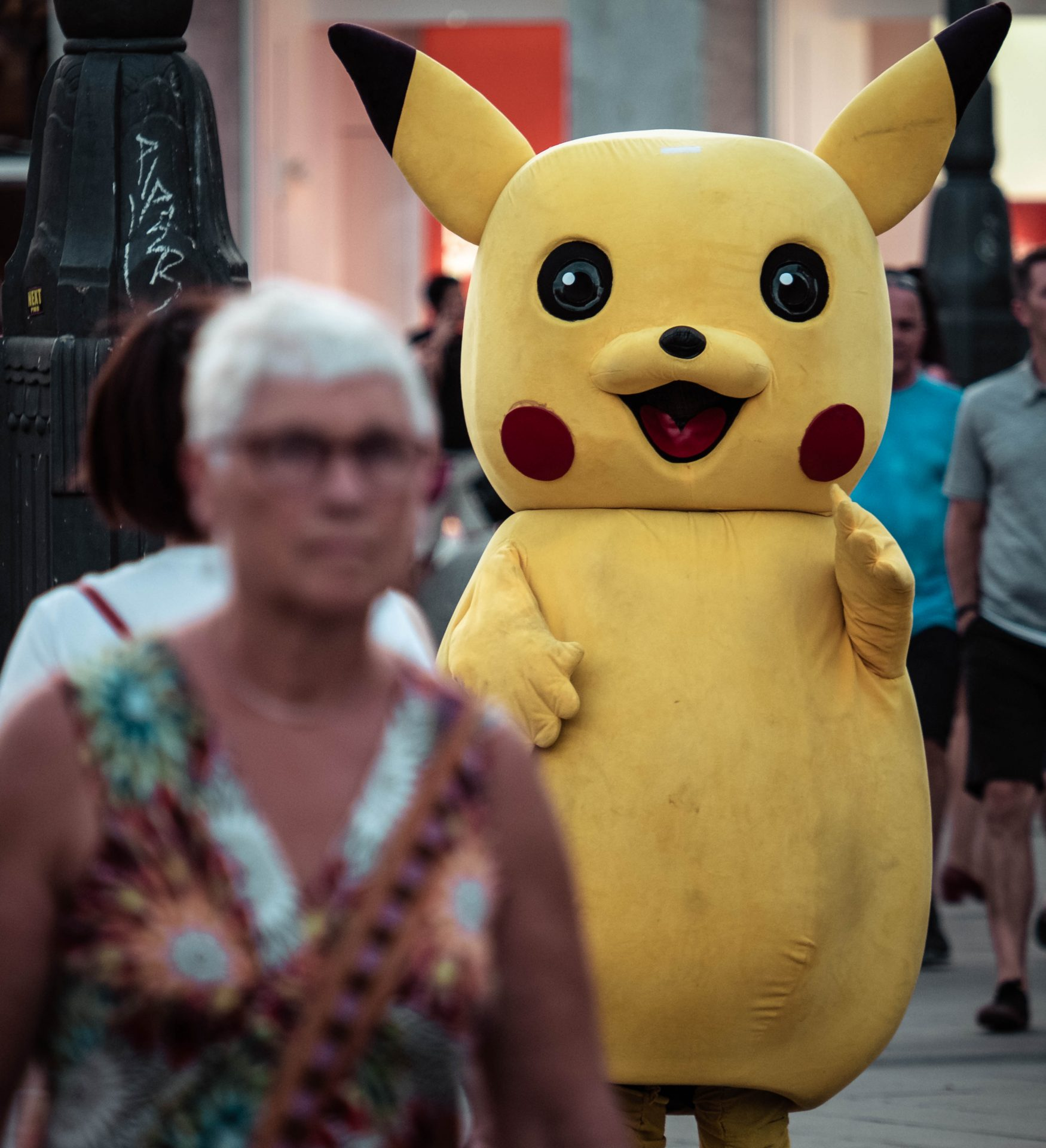 Older women walking in the street with Pikachu in the background photo by Jo Kassis