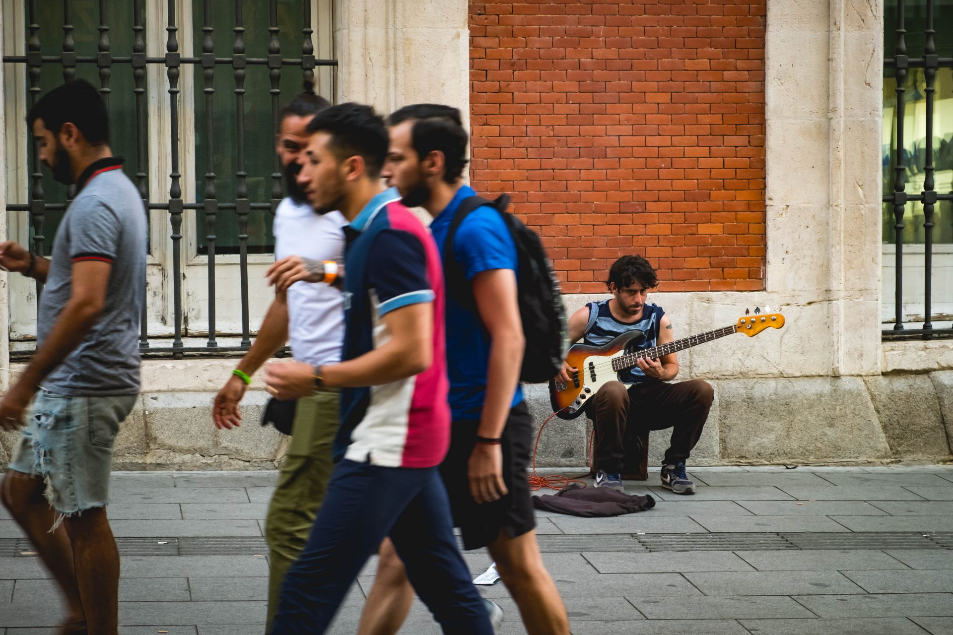 Group of people walking in the streets of Madrid with a guitar player in the background photo by Jo Kassis
