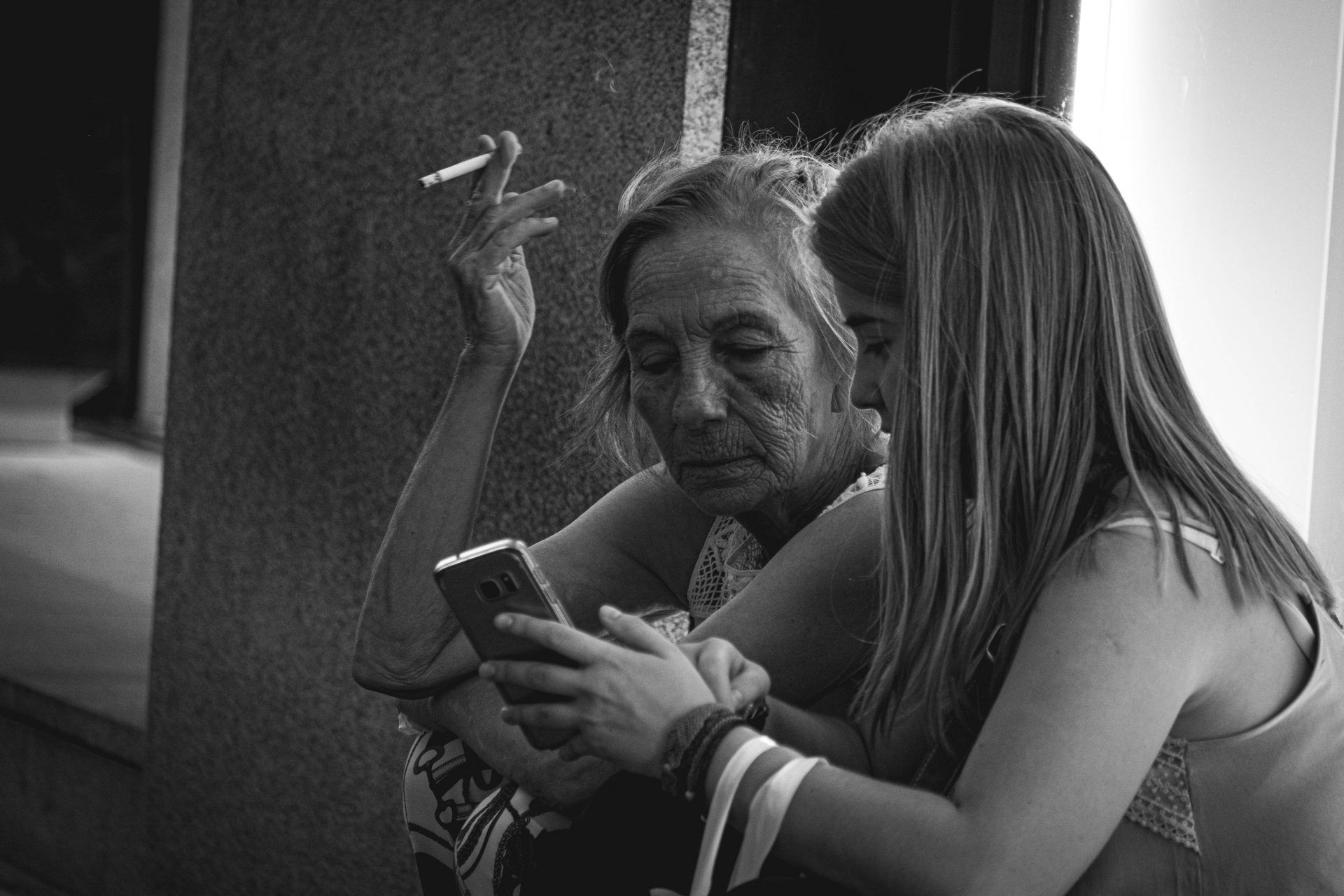Elder women smoking a cigarette sitting with a young girl and staring at a phone photo by Jo Kassis