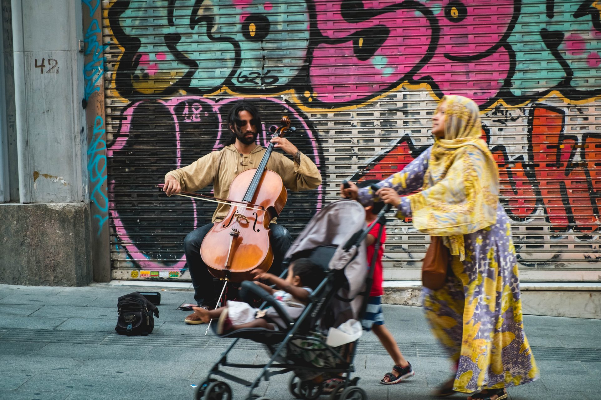 Women walking with her baby and child in front of street performer playing the viola photo by Jo Kassis