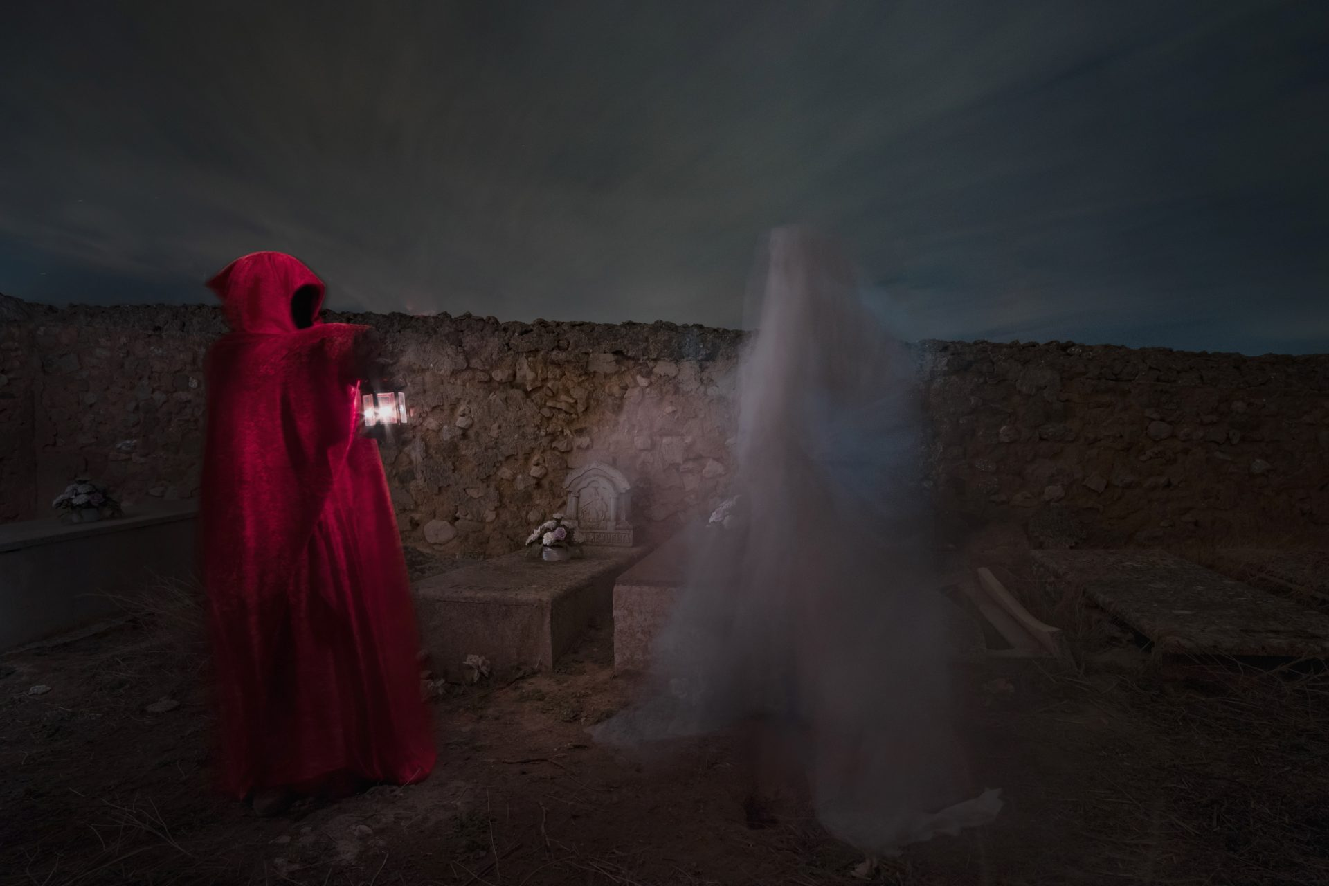 Men in red meeting a ghost at the cemetery photo by Jo Kassis