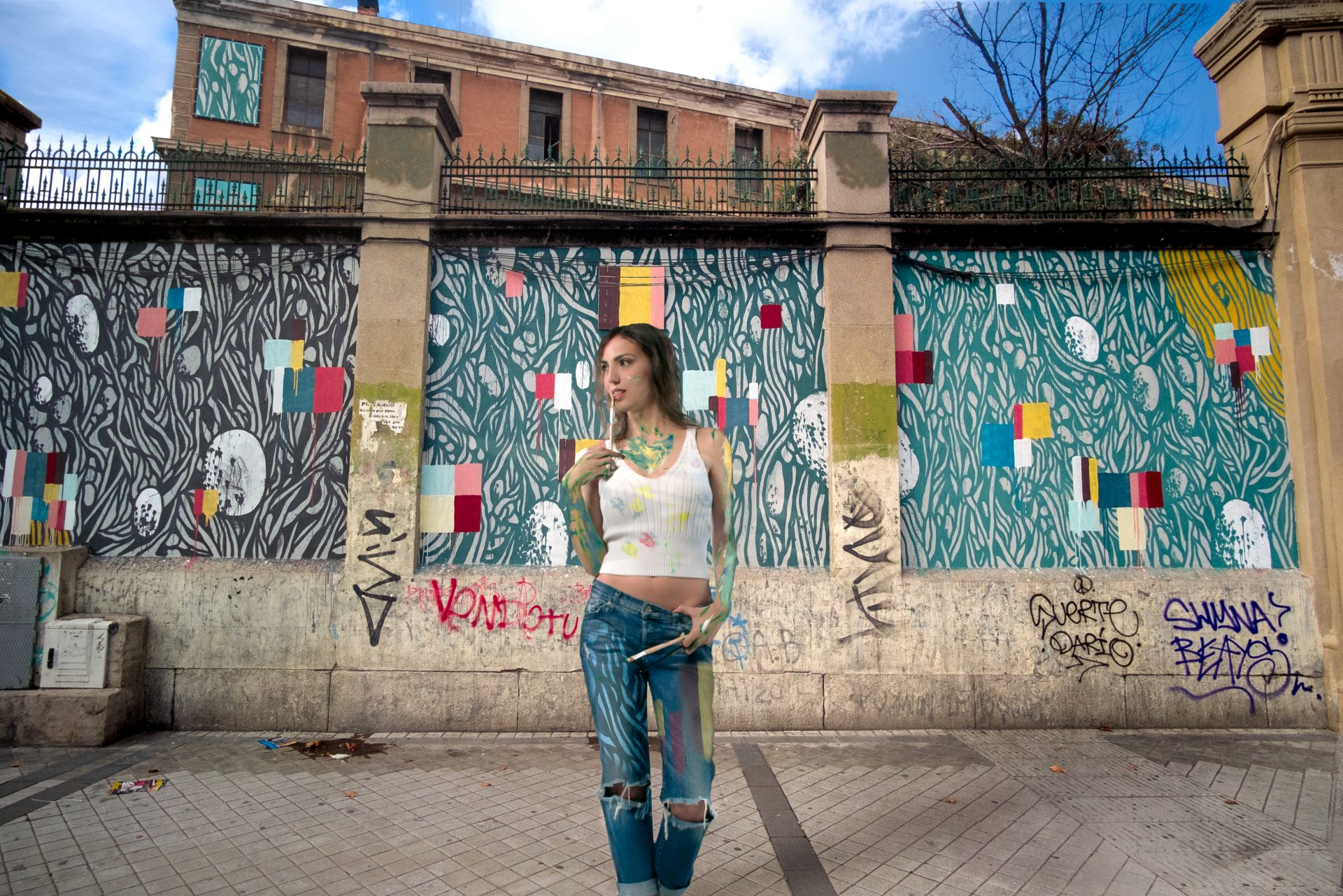 Artistic girl painting wall posing in front of Tabacalera in Madrid photo by Jo Kassis