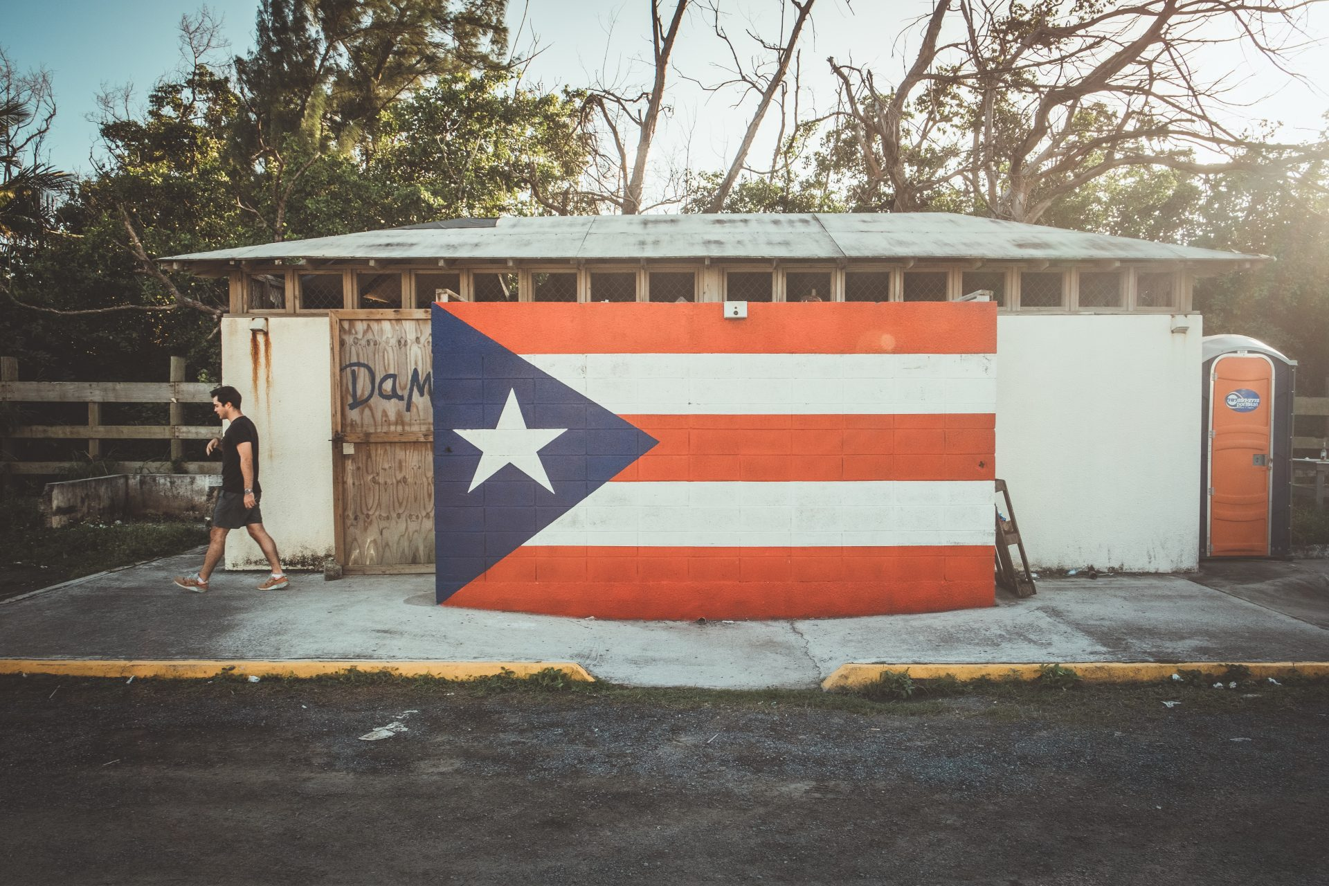 Man walking near a puerto rican flag painted on a wall Photo by Jo Kassis