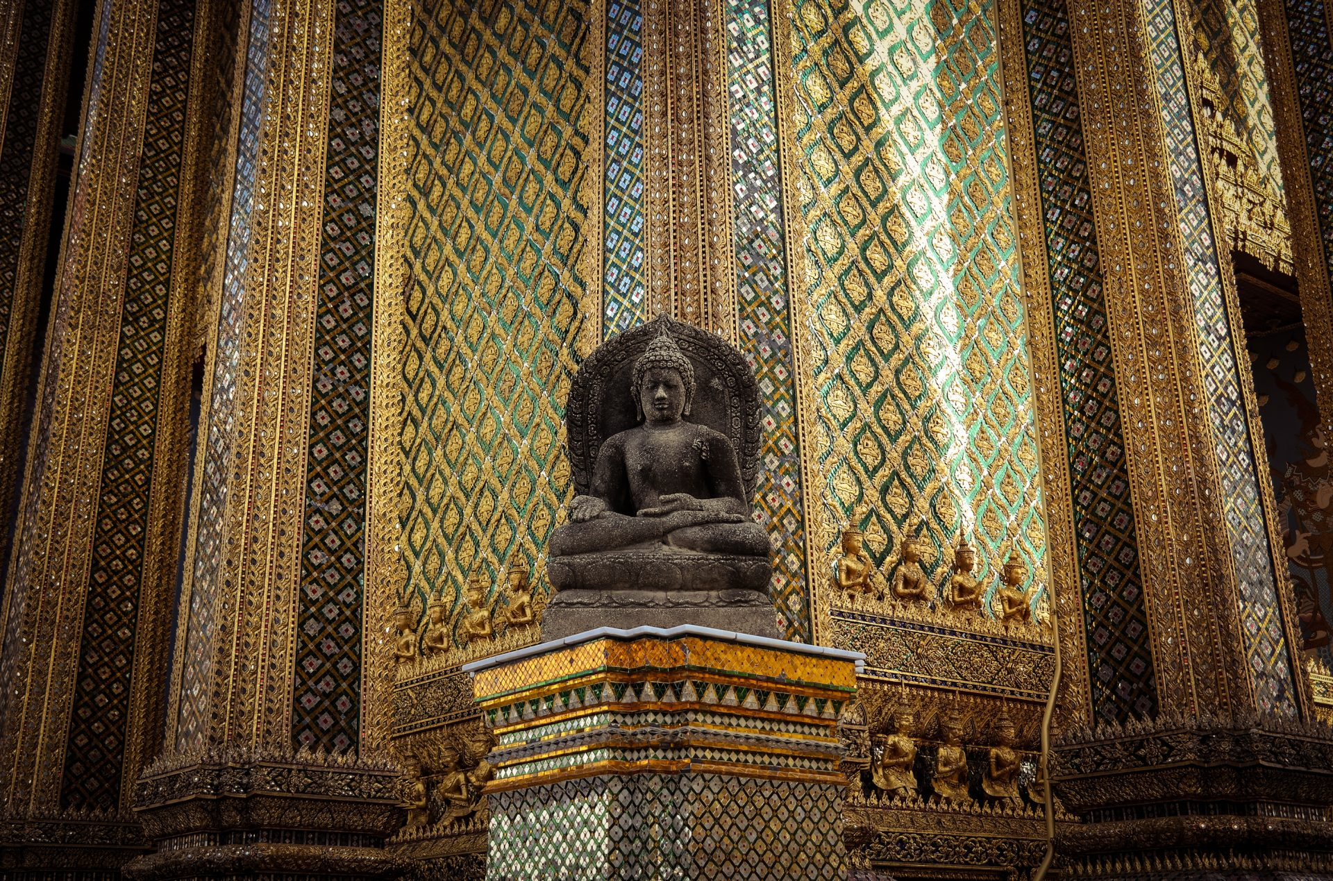 Buddha in a temple in Bangkok thailand with gold background photo by Jo Kassis